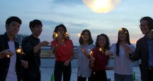 Grupo feliz de amigos jovenes gozar y jugar de la bengala en el partido del top del tejado en la igualación de puesta del sol Cel almacen de video
