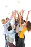 Grupo feliz de amigos novos que jogam o dinheiro no ar fotografia de stock