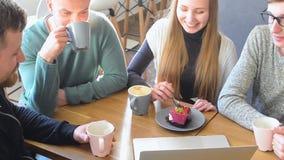 Grupo feliz de amigos o de colegas del negocio que charlan, riendo y usando el ordenador junto en una pequeña barra del café metrajes