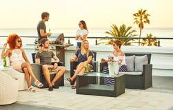 Grupo feliz de amigos próximos que socializam junto em um telhado Imagens de Stock