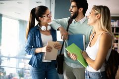 Grupo feliz de amigos que estudam e que falam junto na universidade imagens de stock