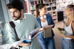 Grupo feliz de amigos que estudam e que falam junto na universidade imagens de stock royalty free