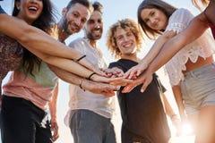 Grupo feliz de amigos que llevan a cabo las manos juntas afuera fotos de archivo