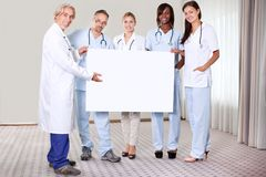 Grupo feliz de doutores que prendem um cartaz em branco fotografia de stock