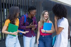 Grupo feliz de estudantes internacionais que andam à universidade foto de stock