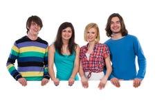 Grupo feliz de estudiantes que se colocan detrás de bandera Imagen de archivo