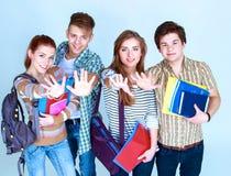 Grupo feliz de estudiantes que sostienen los cuadernos, en el fondo blanco Foto de archivo