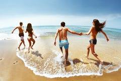 Grupo feliz de funcionamientos de los amigos al mar imagenes de archivo