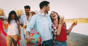 Grupo feliz de gente joven que se divierte en la playa Imágenes de archivo libres de regalías
