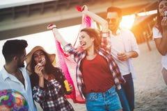 Grupo feliz de gente joven que se divierte en la playa Fotos de archivo