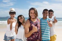 Grupo feliz de hombre multiétnico y de mujeres en la playa Fotografía de archivo libre de regalías