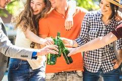 Grupo feliz de los amigos que bebe y que tuesta la cerveza en botella en el aire libre del día soleado - concepto de la amistad c fotos de archivo