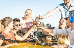 Grupo feliz de los amigos que tuesta bebidas de la moda en el partido de la playa Imagen de archivo libre de regalías