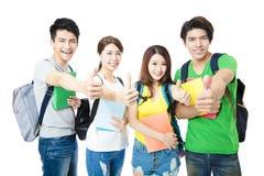 Grupo feliz de los estudiantes universitarios con los pulgares para arriba Fotografía de archivo libre de regalías