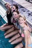 Grupo feliz de mujeres que sientan el poolside Imagenes de archivo