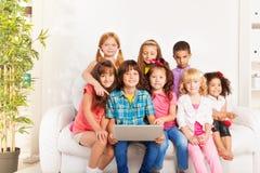 Grupo feliz de niños con el ordenador portátil Foto de archivo libre de regalías