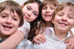 Grupo feliz de niños que abrazan junto Fotografía de archivo