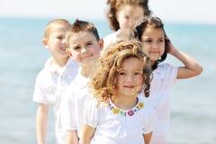 Grupo feliz del niño que juega en la playa fotografía de archivo