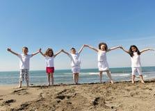 Grupo feliz del niño que juega en la playa imagen de archivo