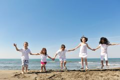 Grupo feliz del niño que juega en la playa imagenes de archivo
