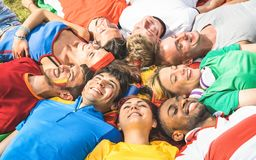 Grupo feliz do amigo que encontra-se no prado após o evento do futebol do mundo - franco fotografia de stock