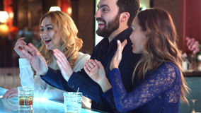 Grupo feliz e atrativo de amigos que conversam e que riem junto em uma barra Fotos de Stock