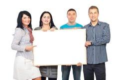 Grupo feliz que prende a bandeira em branco Foto de Stock