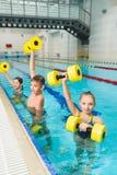 Grupo feliz y sonriente de niños que hacen ejercicios en una piscina Fotos de archivo libres de regalías