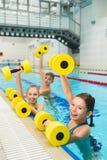 Grupo feliz y sonriente de niños que hacen ejercicios en una piscina Imágenes de archivo libres de regalías