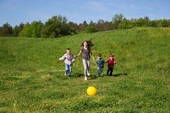Grupo feliz y sonriente de niños que corren a la bola amarilla en el campo verde en Sunny Spring Day Fotografía de archivo