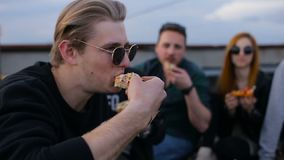 Grupo festivo de amigos bastante jovenes diversos en el tejado en el partido de la pizza metrajes