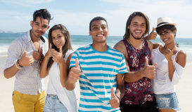 Grupo fresco de hombre multiétnico y de mujeres en la playa Imágenes de archivo libres de regalías