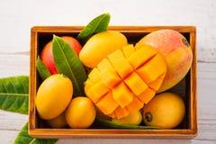 Grupo fresco e bonito do fruto da manga em uma caixa de madeira com os pedaços cortados cortados da manga em um fundo de madeira  Fotos de Stock