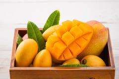 Grupo fresco e bonito do fruto da manga em uma caixa de madeira com os pedaços cortados cortados da manga em um fundo de madeira  Foto de Stock Royalty Free