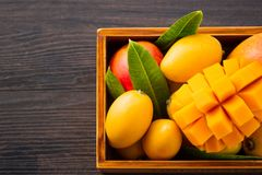 Grupo fresco e bonito do fruto da manga em uma caixa de madeira com os pedaços cortados cortados da manga em um fundo de madeira  Imagens de Stock