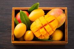 Grupo fresco e bonito do fruto da manga em uma caixa de madeira com os pedaços cortados cortados da manga em um fundo de madeira  Imagens de Stock Royalty Free