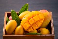 Grupo fresco e bonito do fruto da manga em uma caixa de madeira com os pedaços cortados cortados da manga em um fundo de madeira  Fotografia de Stock
