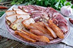 Grupo grande da carne A salsicha fumado caseiro da carne de porco-carne, bacon salgado, basturma desbastou fatias em uma placa de foto de stock royalty free