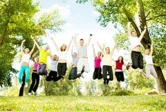 Grupo grande de adolescencias que saltan junto Foto de archivo libre de regalías