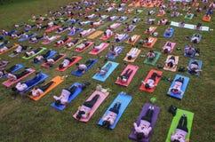 Grupo grande de adultos que asisten a una clase de la yoga afuera en parque Imagenes de archivo