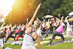 Grupo grande de adultos que atendem a uma classe da ioga fora no parque imagem de stock