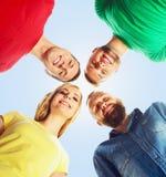 Grupo grande de amigos sonrientes que permanecen junto y que miran c Foto de archivo libre de regalías