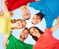 Grupo grande de amigos sonrientes que permanecen junto y que miran c Imagen de archivo