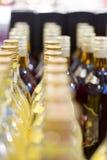Grupo grande de botellas del alcohol en estantes en tienda fotos de archivo