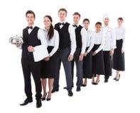 Grupo grande de camareros y de camareras que se colocan en fila foto de archivo