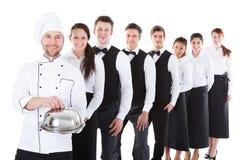 Grupo grande de camareros y de camareras que se colocan en fila imagen de archivo libre de regalías