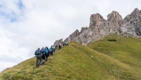 Grupo grande de escaladores y de dos guías de la montaña que caminan hacia el comienzo de una subida en las dolomías imágenes de archivo libres de regalías