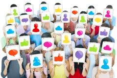 Grupo grande de gente del mundo que sostiene las tabletas de Digitaces con los medios iconos sociales Imagen de archivo libre de regalías