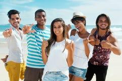 Grupo grande de hombre multiétnico y de mujeres en la playa Fotos de archivo