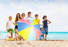 Grupo grande de niños detrás del parasol de playa Foto de archivo